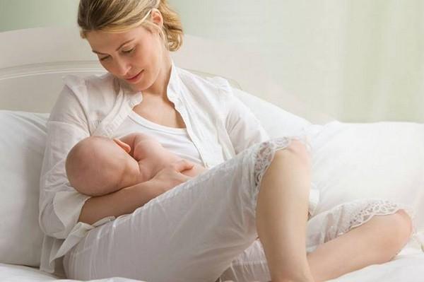 Мама в белой кофте, белой майке и белых бриджах кормит малыша грудью