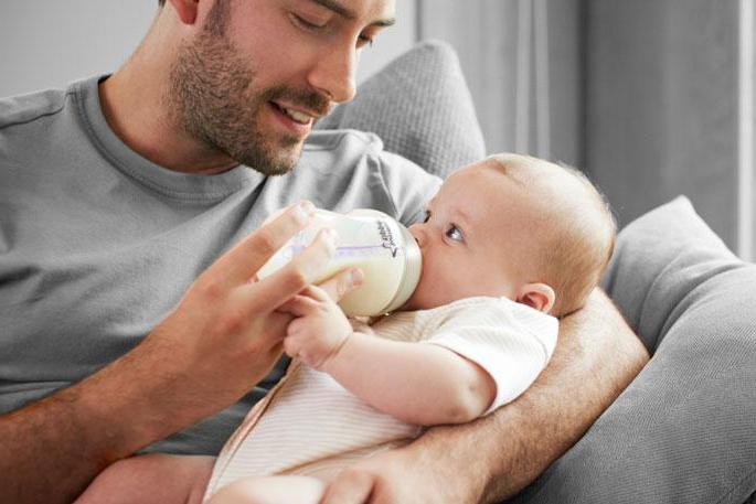 Папа в серой футболке кормит ребёнка из бутылочки
