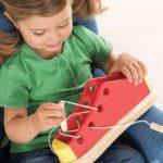 Девочка учится затягивать и завязывать шнурки