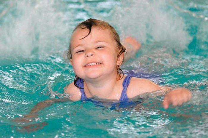 Девочка плавает в бассейне