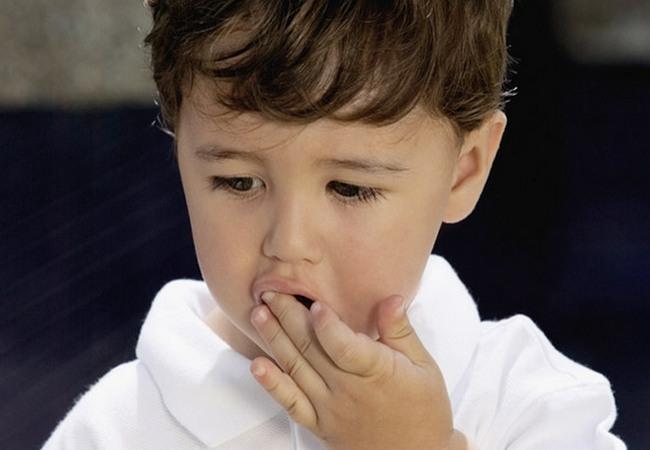 Малыш рукой пытается что-то достать изо рта
