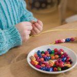 Ребёнок нанизывает бусы на нить