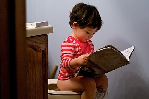 Ребёнок сидит на унитазе