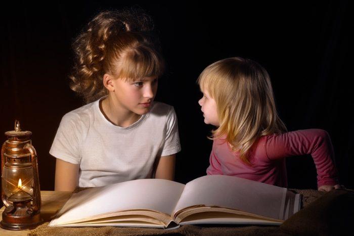 Девочка-подросток показывает сестренке магические для нее атрибуты — старинную лампаду и альбом