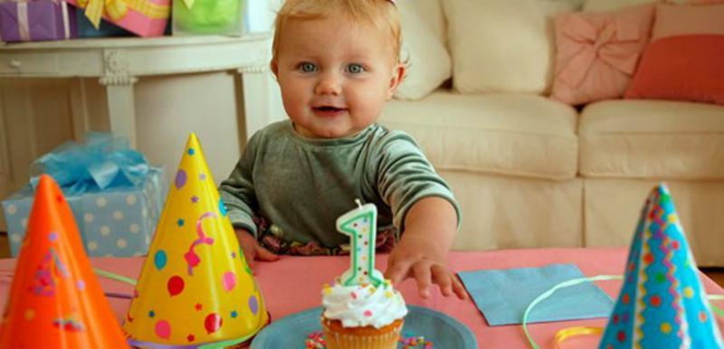 Мальчик, праздничные колпаки и кекс с цифрой 1