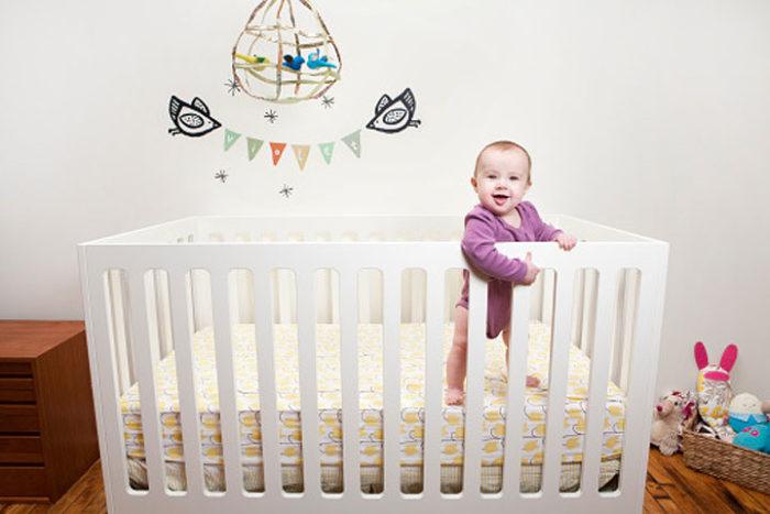 Малыш стоит в кроватке