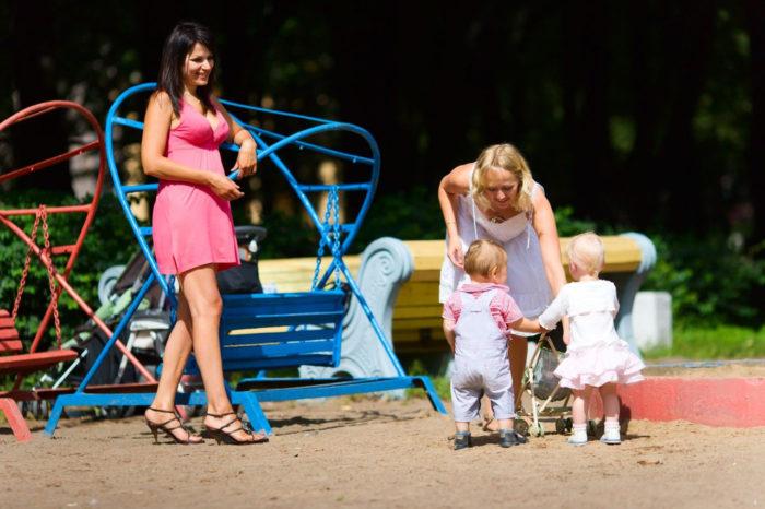 Молодые мамы с малышами на детской площадке