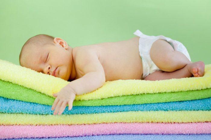 Новорождённый спит в подгузнике