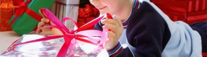 Мальчик развязывает красную ленту на коробке с подарком