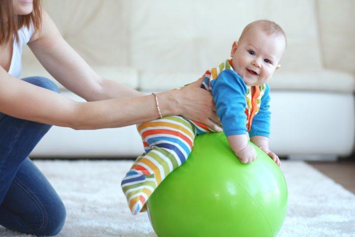 Ребёнок 8 месяцев делает зарядку на фитболе