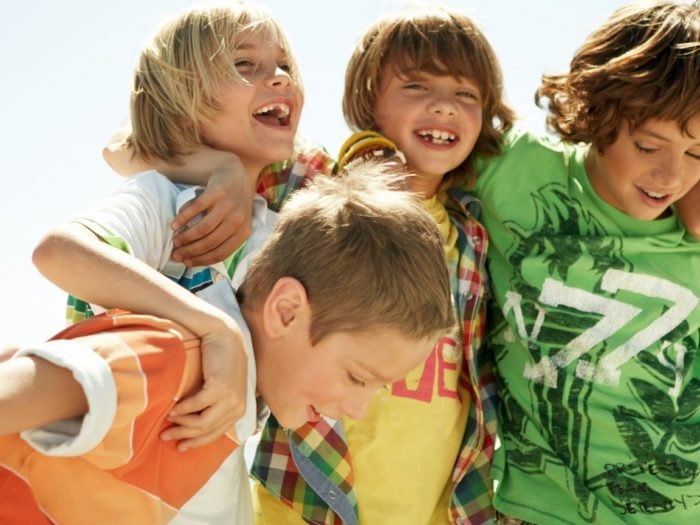 Четыре мальчика обнялись и смеются