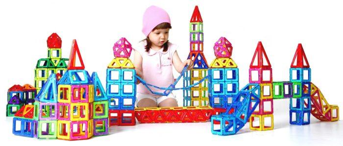 Девочка строит башенку из магформерсов