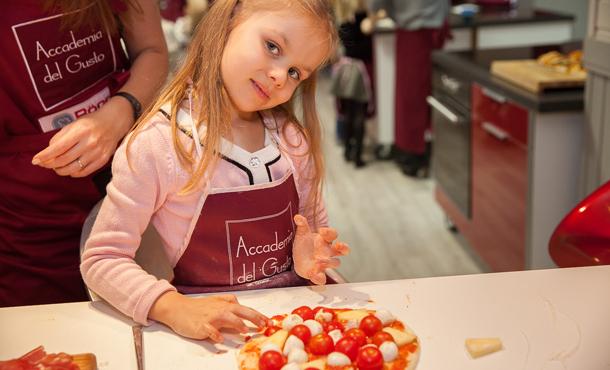 Девочка украшает пиццу