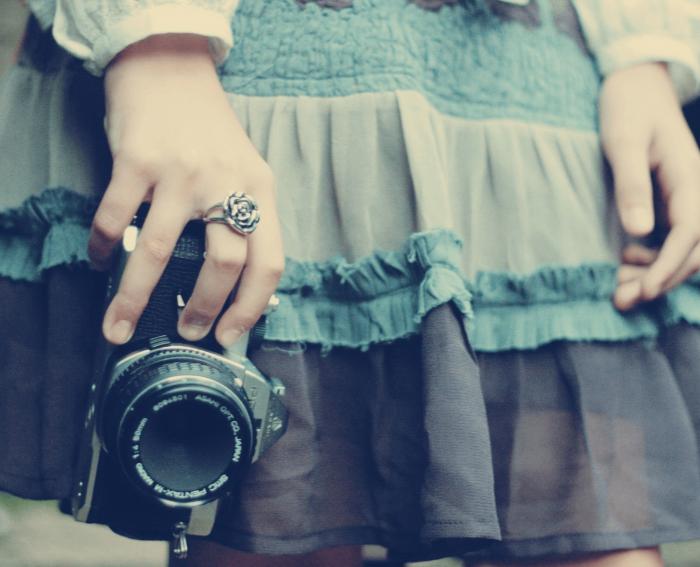 Девочка в юбке держит фотоаппарат