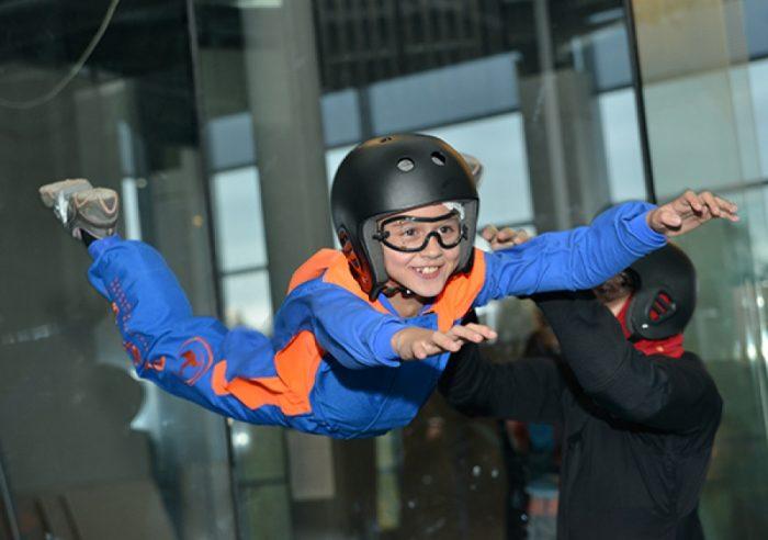 Инструктор поддерживает девочку в аэротрубе