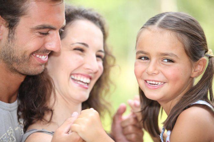Мама, папа и девочка смеются