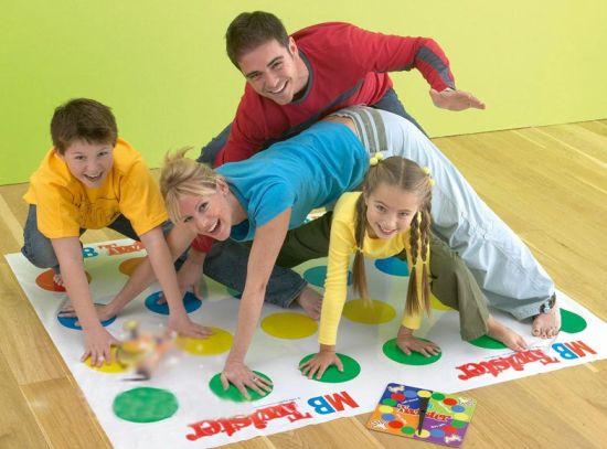 Папа, мама и двое детей играют в Твистер