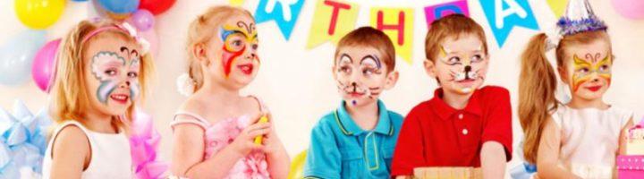 Пятеро детей с аквагримом сидят за праздничным столом