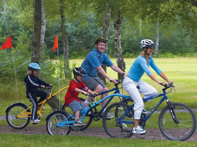 Родители и двое детей на велосипедах