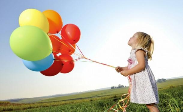 Девочка на поляне держит связку шариков
