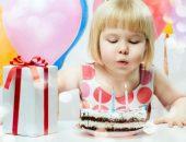 Девочка задувает три свечи на торте