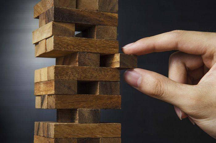 Пальцы вытаскивают элемент башни Дженга