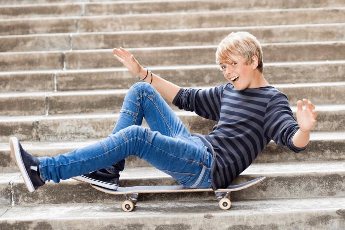 Парень сидит на ступеньках на скейте
