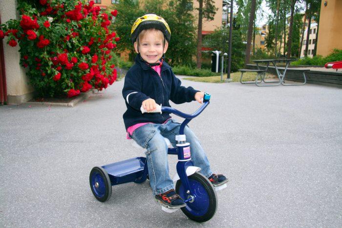 Мальчик в шлеме на трёхколёсном велосипеде