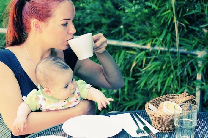 Мама пьёт чай с малышом на руках