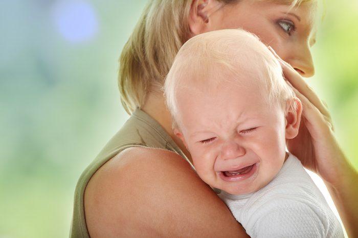 Плачущий младенец на руках у женщины