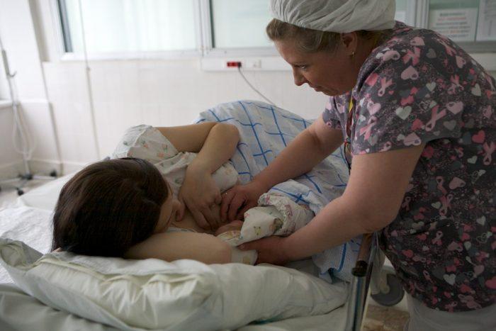 Акушерка прикладывает новорождённого к груди матери