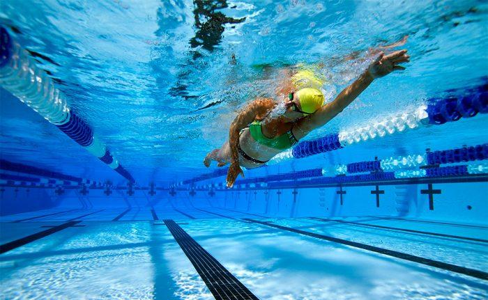 Женщна плавает в бассейне
