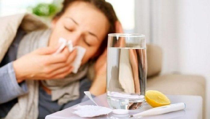 Болеющая женщина, стакан с водой, лимон и градусник