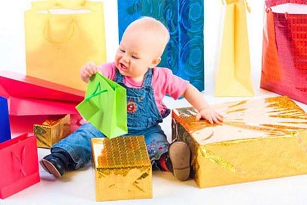 Мальчик держит в руках зелёный подарочный пакет