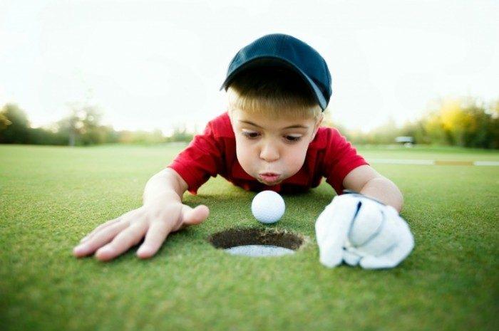 Мальчик дует на мяч для гольфа