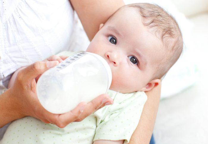 Мама кормит младенца из бутылочки