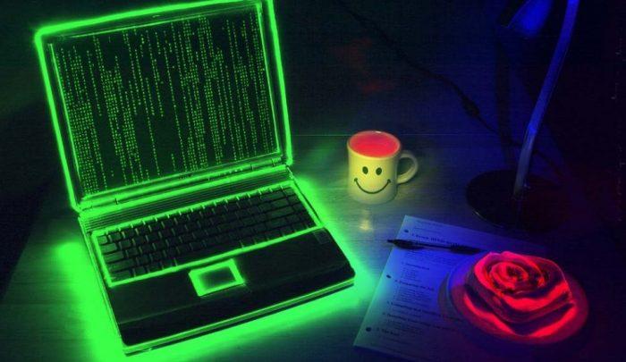 Ноутбук на столе светится зелёным цветом