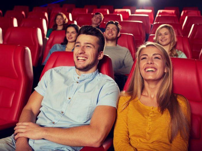 Люди смеются в кинозале