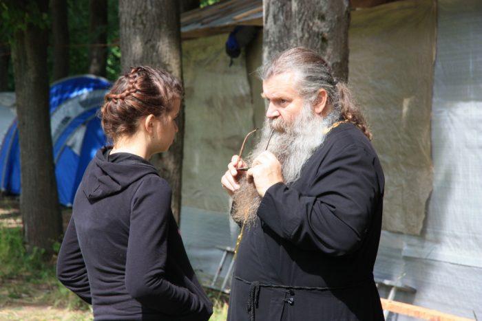 Женщина разговаривает со священником