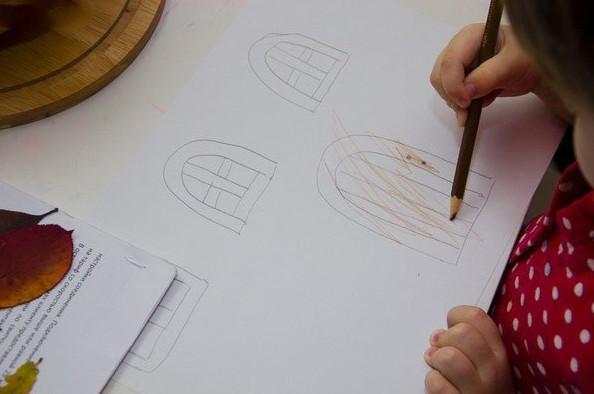 Ребёнок раскрашивает нарисованную на бумаге дверь