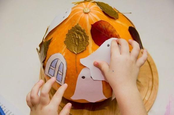Ребёнок прикрепляет к домику-тыкве бумажных приведений (листья и окно уже наклеены)