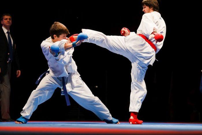 Соревнование по карате: один спортсмен наносит другому удар ногой в голову