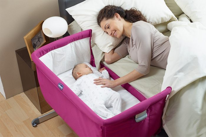 Семимесячный малыш в приставной кроватке, рядом на кровати мама