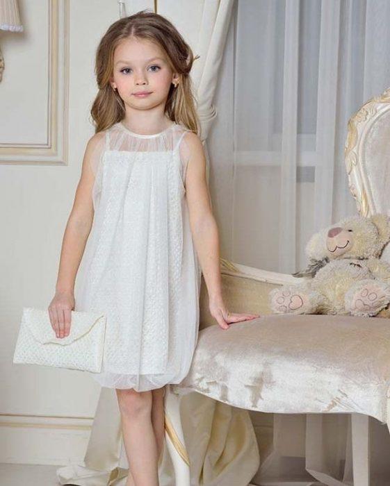 Девочка в белом нарядном платье с клатчем