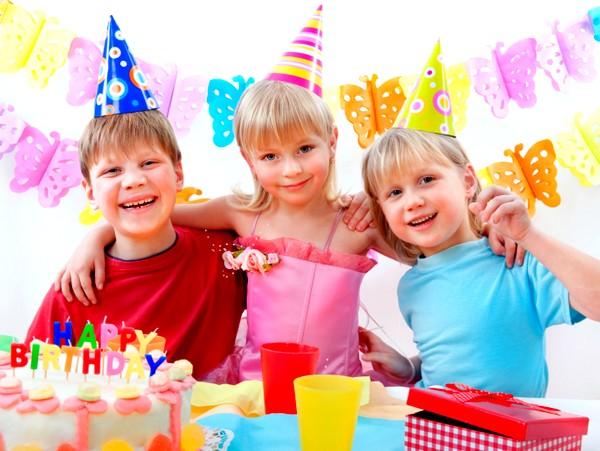 Два мальчика и девочка за праздничным столом с тортом