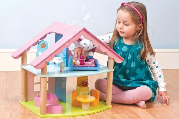 Девочка играет с кукольным домиком