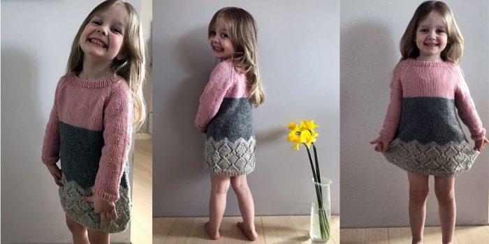 Девочка позирует в розово-сером вязаном платье
