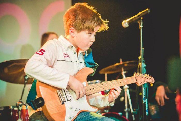 Мальчик с гитарой на сцене