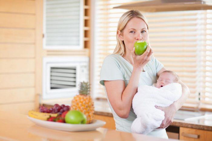Женщина ест яблоко с малышом на руках