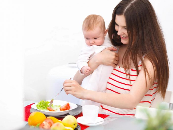 Женщина ест салат с младенцем на руках